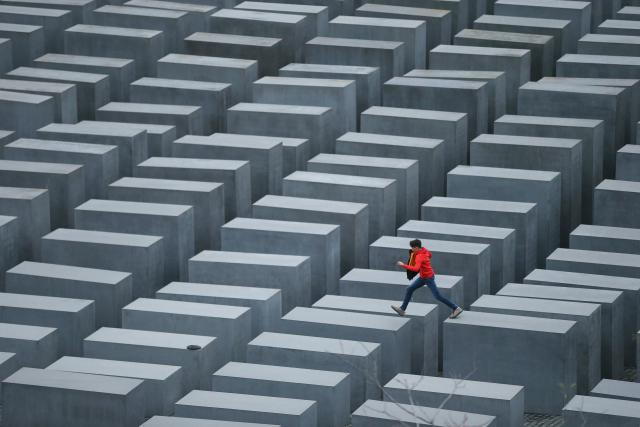 BERLIN, GERMANY - OCTOBER 28: A boy hops from one to another of the 2,711 stellae at the Memorial to the Murdered Jews of Europe, also called the Holocaust Memorial, on October 28, 2013 in Berlin, Germany. The monument, located in the city center, was designed by American architect Peter Eisenman and commemorates the 6 million Jews murdered by the Nazis. (Photo by Sean Gallup/Getty Images)